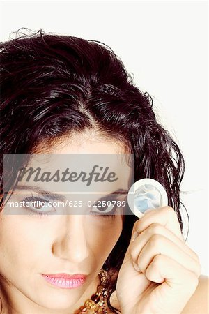 Portrait of a young woman holding a condom Stock Photo - Premium Royalty-Free, Image code: 625-01250789