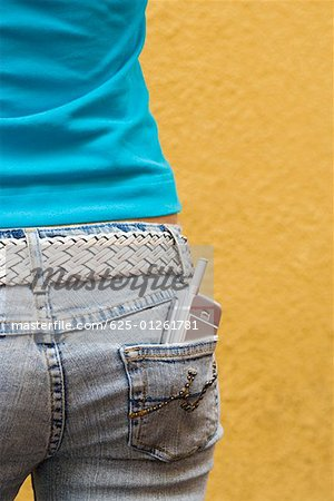 Close-up of a mobile phone in a teenage girl's back pocket Stock Photo - Premium Royalty-Free, Image code: 625-01261781