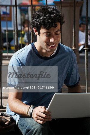 Close-up of a young man using a laptop and smiling Stock Photo - Premium Royalty-Free, Image code: 625-01746699