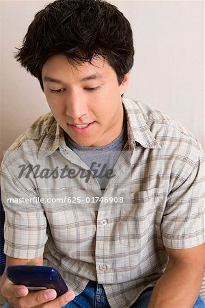 Close-up of a young man holding a mobile phone and text messaging Stock Photo - Premium Royalty-Free, Image code: 625-01746908