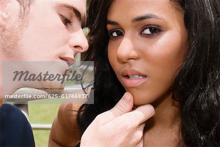 Close-up of a young man about to kiss a teenage girl Stock Photo - Premium Royalty-Free, Image code: 625-01746937