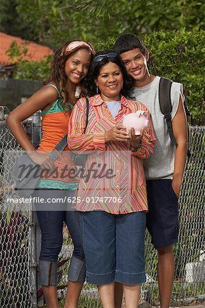 Portrait of a mature woman holding a piggy bank while standing with her daughter and son Stock Photo - Premium Royalty-Free, Image code: 625-01747706