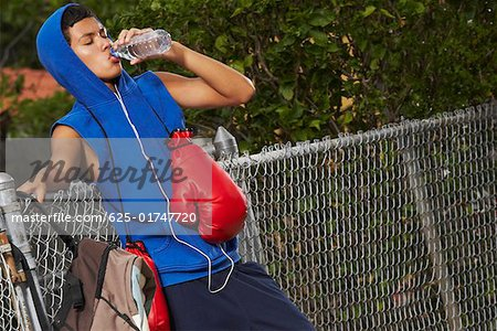 Side profile of a teenage boy listening an ipod and drinking water from a bottle Stock Photo - Premium Royalty-Free, Image code: 625-01747720