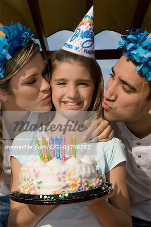 Portrait of a girl holding a birthday cake and her parents kissing her Stock Photo - Premium Royalty-Free, Image code: 625-01748253