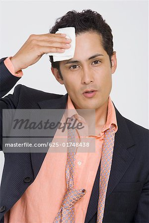 Portrait of a businessman wiping sweat with a handkerchief Stock Photo - Premium Royalty-Free, Image code: 625-01748438