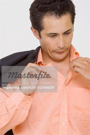 Close-up of a businessman blowing in a shirt Stock Photo - Premium Royalty-Free, Image code: 625-01748439