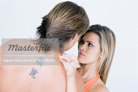 Rear view of a young man with a young woman holding a condom Stock Photo - Premium Royalty-Free, Image code: 625-01748652