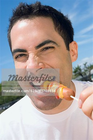 Portrait of a mid adult man eating a sausage Stock Photo - Premium Royalty-Free, Image code: 625-01748834