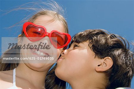 Low angle view of a boy kissing a girl Stock Photo - Premium Royalty-Free, Image code: 625-01749035