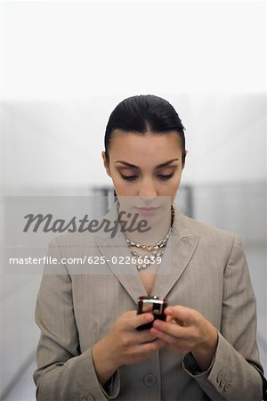 Close-up of a businesswoman text messaging at an airport Stock Photo - Premium Royalty-Free, Image code: 625-02266639