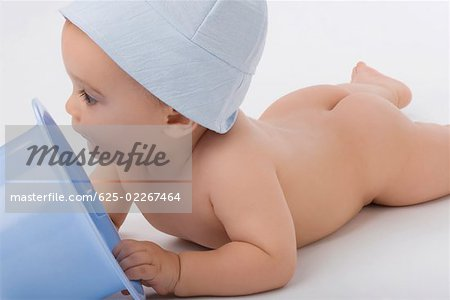 Close-up of a baby boy playing with a bucket Stock Photo - Premium Royalty-Free, Image code: 625-02267464