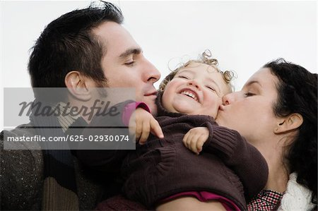 Close-up of a couple kissing their daughter Stock Photo - Premium Royalty-Free, Image code: 625-02930074
