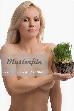 Portrait of a young woman holding wheatgrass Stock Photo - Premium Royalty-Free, Image code: 625-02930682