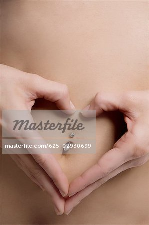 Close-up of a young woman forming heart shape with her fingers on her belly button Stock Photo - Premium Royalty-Free, Image code: 625-02930699