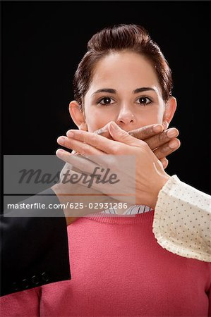 Close-up of a person's hand covering a businesswoman's mouth Stock Photo - Premium Royalty-Free, Image code: 625-02931286