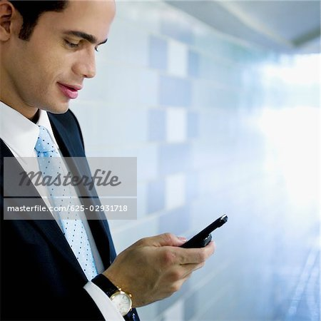 Close-up of a businessman text messaging Stock Photo - Premium Royalty-Free, Image code: 625-02931718