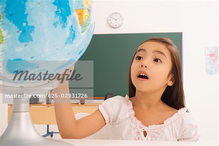 Girl looking at a desktop globe Stock Photo - Premium Royalty-Free, Image code: 625-02931726