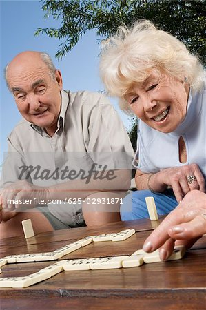 Senior couple playing dice game Stock Photo - Premium Royalty-Free, Image code: 625-02931871