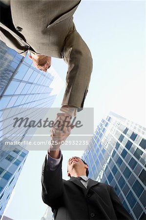 Low angle view of two businessmen shaking hands and smiling Stock Photo - Premium Royalty-Free, Image code: 625-02932235