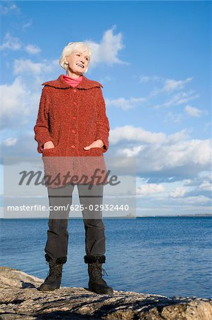 Senior woman standing on a rock at the coast Stock Photo - Premium Royalty-Free, Image code: 625-02932440