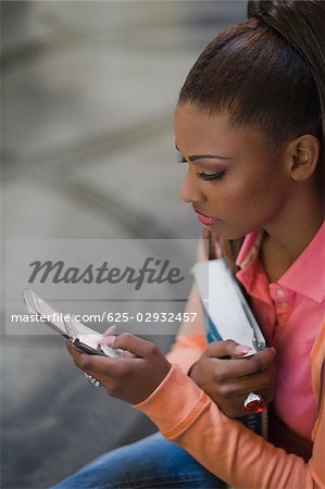 Close-up of a young woman text messaging Stock Photo - Premium Royalty-Free, Image code: 625-02932457