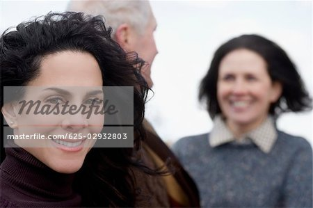 Close-up of a mature woman with a couple behind her Stock Photo - Premium Royalty-Free, Image code: 625-02932803