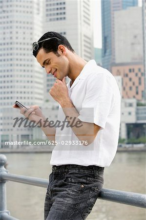 Side profile of a mid adult man text messaging and smiling Stock Photo - Premium Royalty-Free, Image code: 625-02933176