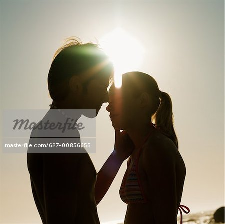 Side view of young couple kissing (silhouette) Stock Photo - Premium Royalty-Free, Image code: 627-00856655