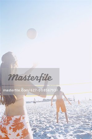 Rear view of a group of young men and women playing volleyball on the beach Stock Photo - Premium Royalty-Free, Image code: 627-00856793