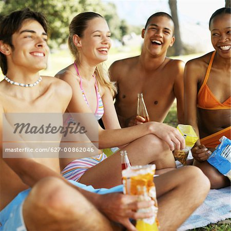 Teenage girls and boys eating crisps and drinking soda Stock Photo - Premium Royalty-Free, Image code: 627-00862046