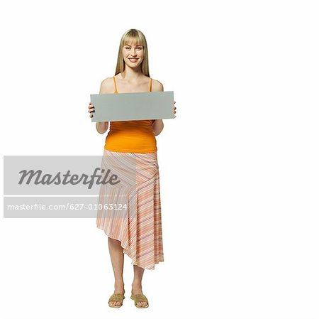 Front view of woman holding blank card Stock Photo - Premium Royalty-Free, Image code: 627-01063124
