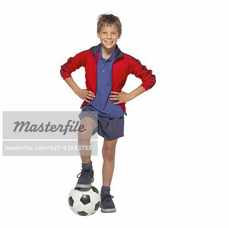 front view portrait of a boy (11- 12) holding a soccer-ball with his leg Stock Photo - Premium Royalty-Free, Image code: 627-01063733