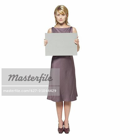Portrait of young woman holding blank card Stock Photo - Premium Royalty-Free, Image code: 627-01064429