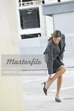 Businesswoman rubbing her leg and holding mobile phone Stock Photo - Premium Royalty-Free, Image code: 627-01066988