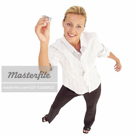 Elevated view of a woman holding a paper airplane Stock Photo - Premium Royalty-Free, Image code: 627-01068913