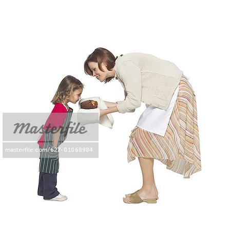 Side view of mother showing baked bread to daughter (4-5) Stock Photo - Premium Royalty-Free, Image code: 627-01068984