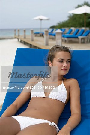 Young girl wearing bikini, sitting on deck chair at the beach Stock Photo - Premium Royalty-Free, Image code: 628-00919202