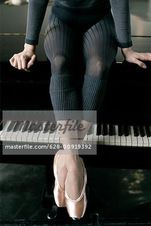 A female ballet dancer sitting on a piano