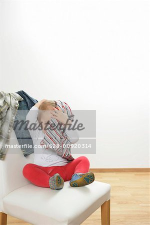 Baby boy hiding under a shirt Stock Photo - Premium Royalty-Free, Image code: 628-00920314