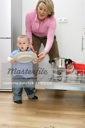 Son and mother emptying a dishwasher Stock Photo - Premium Royalty-Free, Image code: 628-00920355