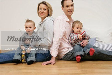 Father and mother sitting back to back, sons on the laps Stock Photo - Premium Royalty-Free, Image code: 628-00920380