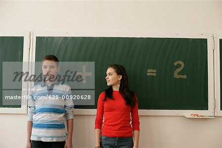 Two pupils standing in front of a blackboard, arithmetic problem in background Stock Photo - Premium Royalty-Free, Image code: 628-00920628