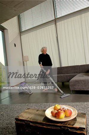 Senior woman vacuuming living room Stock Photo - Premium Royalty-Free, Image code: 628-02615257