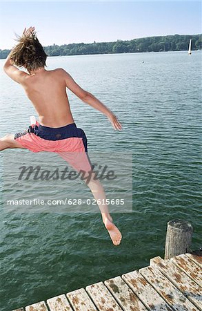 Boy jumping into Water from a wooden Footbridge - Salutation - Fun - Summer - Swimming Stock Photo - Premium Royalty-Free, Image code: 628-02615685