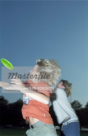 Two Boys trying to catch a Frisbee out of the Air - Game - Leisure Time - Youth - Park - Twilight Stock Photo - Premium Royalty-Free, Image code: 628-02615726
