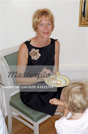Blonde Woman eating Cake with a Child - Dessert - Family Party Stock Photo - Premium Royalty-Free, Image code: 628-02615758