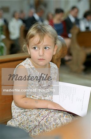Little Girl with a Songbook in her Lap sitting on a Bench in a Church - Ceremony - Baptism - Christianity - Childhood Stock Photo - Premium Royalty-Free, Image code: 628-02615785