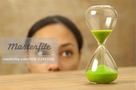 Woman looking at hourglass with green sand Stock Photo - Premium Royalty-Free, Image code: 628-02953551