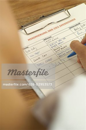 Woman signing a list for minimization of CO2 emissions Stock Photo - Premium Royalty-Free, Image code: 628-02953573