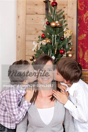 Boy and girl kissing their mother at Christmas tree Stock Photo - Premium Royalty-Free, Image code: 628-02953692